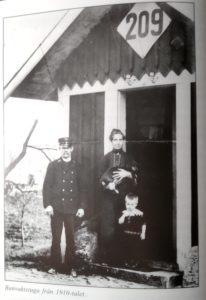 Banvaktarfamilj i dörröppningen till sin lilla stuga.